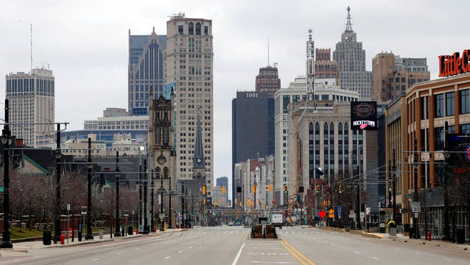 In this March 24, 2020, file photo, Woodward Avenue is shown nearly empty in Detroit. Before the coronavirus showed up, downtown Detroit was returning to its roots as a vibrant city center, motoring away from its past as the model of urban ruin. Now, with the coronavirus forcing many office workers to their homes in the suburbs, those who remain wonder if revitalization will ever return.