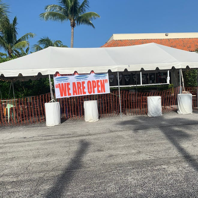 A tent is set up in the parking lot outside Double Roads Tavern in Jupiter.