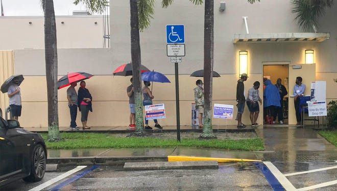 Early morning voters line up Monday under their umbrellas outside of the Wellington Library to cast their votes in the 2020 presidential election. BILL INGRAM/PALM BEACH POST