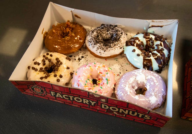 Hot donuts are made to order at the Factory Donuts in Wellington, October 14, 2020.