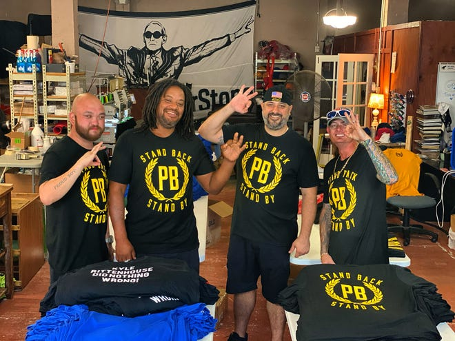 "Bobby Pickles, third from left, displays the OK hand sign with other Proud Boys at his business, FAT ENZO T-SHIrTS, in downtown West Palm Beach. Groups that monitor extremism claim the three fingers extending from the hand form the letter ""W""—for white. Proud Boys claim there is no meaning behind the use of the hand signal beyond annoying and agitating liberals."