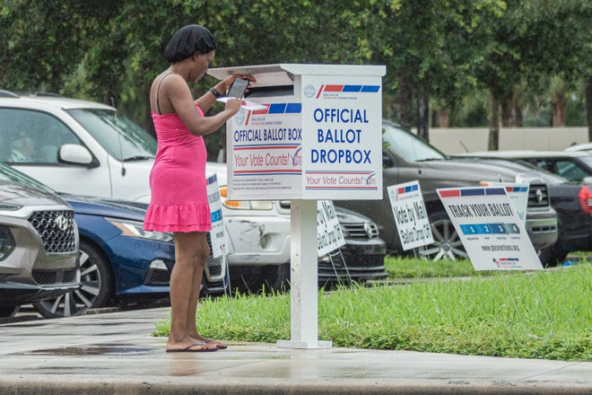 A woman drops her mail-in ballot at the official ballot drop box at the Supervisor of Elections Office in West Palm Beach on Oct. 21.