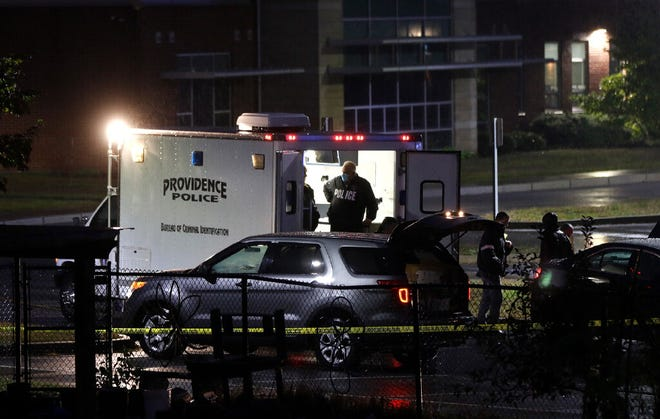 The Providence police investigate the scene of a triple shooting that left one person dead October 13 in the parking lot of the Rhode Island School for the Deaf. The police Tuesday seized a handgun after spotting a group of young men loitering in the area.