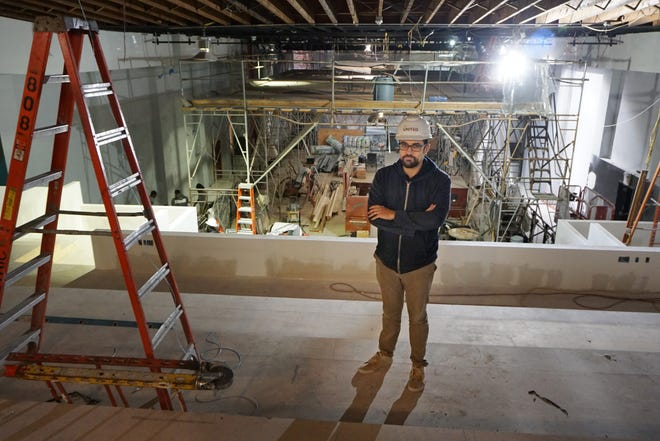Tony Nunes, artistic director for the United Theatre in Westerly, stands amid reconstruction work at the venue, which is expected to reopen in May 2021. Nunes is on the upper level, where there will be tiered seating; in the background is a large multi-use arts space.