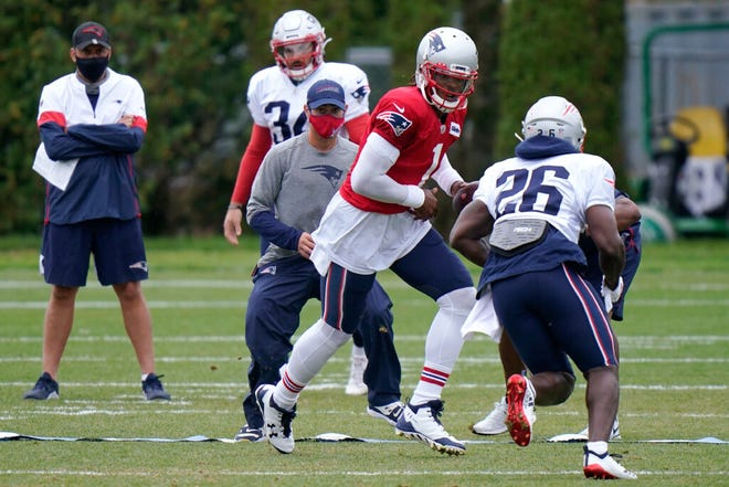 New England Patriots quarterback Cam Newton (1) hands off to running back Sony Michel (26) during an NFL football training camp practice, Thursday Aug. 27, 2020 in Foxborough, Mass.