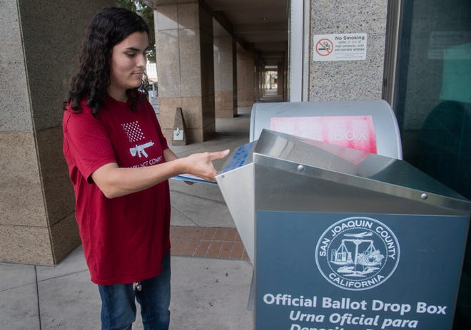 Sandra Ramirez of Stockton casts an early vote by dropping her mail-in ballot at the drop-off box outside the main entrance to the San Joaquin County Administration Building on Oct. 9 in downtown Stockton.