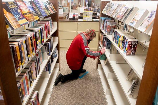 Austin Johnson, circulation clerk, arranges books at the Garrettsville Library.