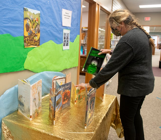 Robin Jones-Taraska, a children's librarian at Portage County District Library, Garrettsville, sets up a display.