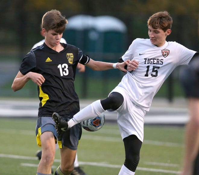 Drew Tyler (13) of Perry fights for control of the ball with Michael Ames (15) of Massillon during their game at Perry on Wednesday, Oct. 21, 2020.