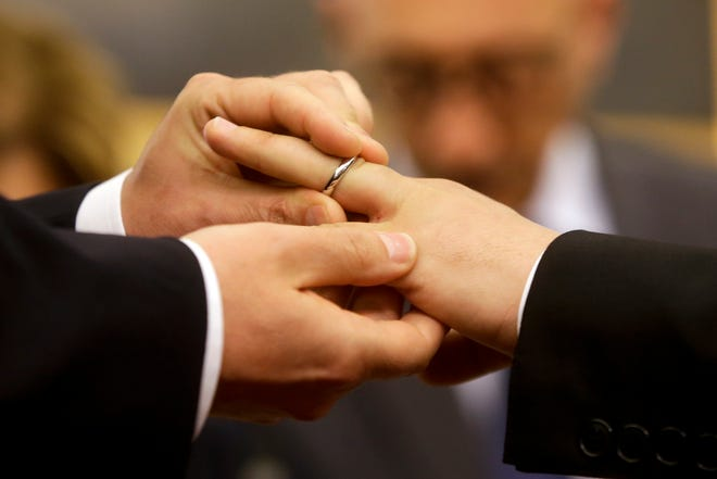FILE - In this May 21, 2015 file photo, Mauro Cioffari, left, puts a wedding ring on his partner Davide Conti's finger as their civil union is being registered by a municipality officer during a ceremony in Rome's Campidoglio Capitol Hill. Pope Francis endorsed same-sex civil unions for the first time as pope while being interviewed for the feature-length documentary 'Francesco,' which premiered Wednesday, Oct. 21 2020 at the Rome Film Festival. (AP Photo/Gregorio Borgia, file)