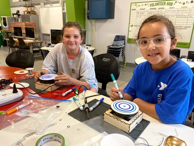 Olivia and Pepper take their homemade art bots for a spin during a STEM Saturdays class.