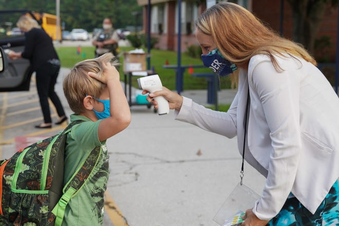 Principal April Perkins takes a student's temperature as children return to school at Rocky Point Elementary School in Pender County on Aug. 18, 2020. Each student was screened before entering the school and masks were mandatory.