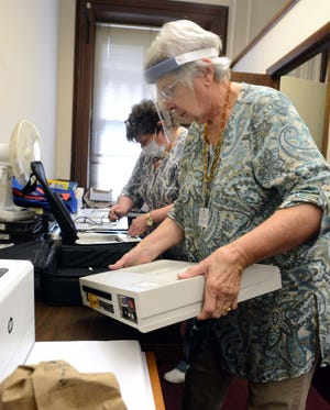 Dianne Slopak, Republican registrar, right, and Cate Larkin, Democratic deputy registrar, prepare to charge some of 22 voting machines Wednesday at Norwich City Hall for the presidential election. [John Shishmanian/ NorwichBulletin.com]