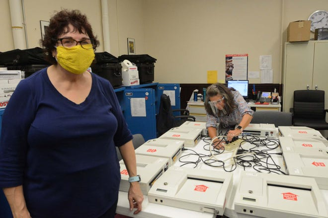 JoAnn Merolla-Martin, left, head moderator and Linda Minter, Republican deputy registrar, prepare to charge some of 22 voting machines Wednesday at Norwich City Hall for the presidential election. [John Shishmanian/ NorwichBulletin.com]