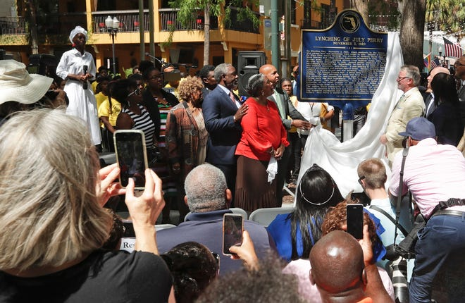 In this June 21, 2019 photo, descendants of July Perry along with local elected officials and residents attend a ceremony unveiling a historical marker in Orlando. Perry was lynched by a white mob after helping a friend trying to vote. After Perry was lynched, the mob laid siege to the black section of Ocoee, killing dozens.