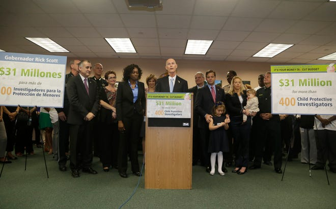 Florida Gov. Rick Scott, center, speaks during a news conference at the Department of Children and Families in 2014 in Miami.