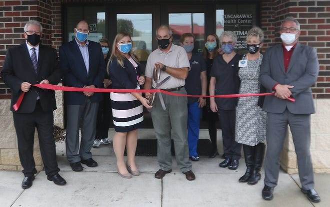 Doctors Keely Telquist and James Moore are ready to cut the ribbon for the Tuscarawas Regional Health Center of Aultman Orrville Hospital during the ceremony Wednesday afternoon. (TimesReporter.com / Jim Cummings)