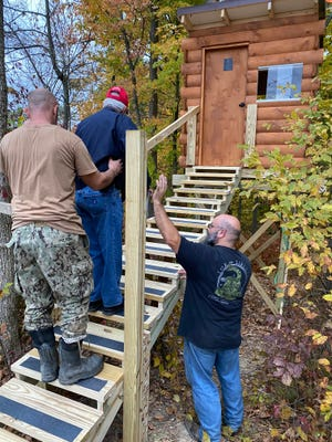 Navy veteran Bob Fulton gets a hand getting to his new tree stand.