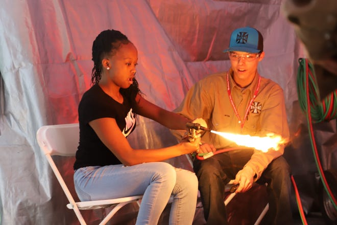 A Tuscaloosa County School System welding student shows an unnamed eighth grader how to light a welding torch during the 2019 Worlds of Work Career Expo at Shelton State Community College in this photo submitted by West Alabama Works. Welding is one of the in-demand career technical education courses in the Tuscaloosa County School System.