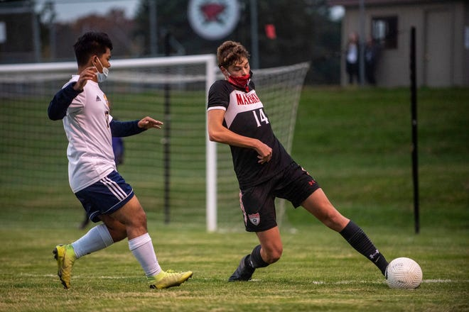 Marshall junior Marcos Eshuis (14) controls the ball while Battle Creek Central senior Richard Lian (15) covers him during the Division 2 District Semifinal at Marshall High School on Tuesday, Oct. 20, 2020 in Marshall, Mich. Marshall defeated Battle Creek Central 6-3.