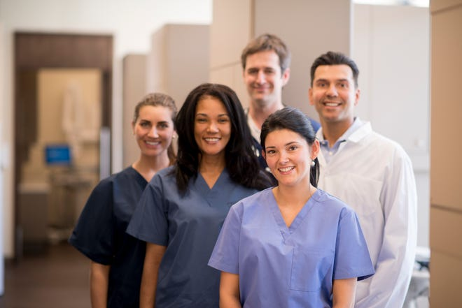 A group of doctors, nurses, and or dentists and professional assistants posing for a picture in a medical clinic.