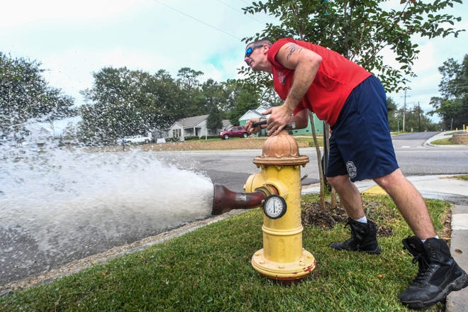This stock photo shows a man testing the water pressure of a fire hydrant.