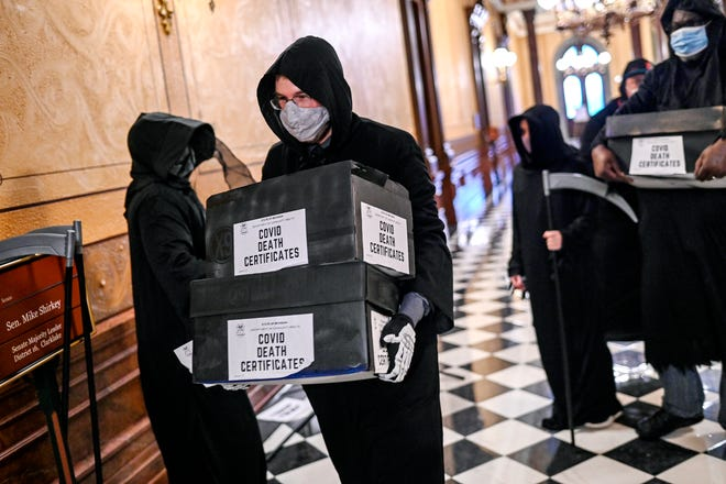 Activists dressed as the Grim Reaper deliver 30,000 blank death certificates to Sen. Mike Shirkey's office in protest of his COVID-19 'herd immunity' comments on Wednesday, Oct. 21, 2020, at the Capitol in Lansing.