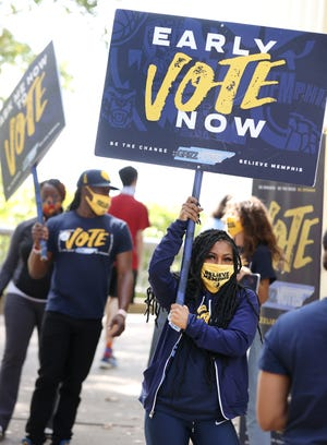 Grizz Girls dancer Jaylen Boga waves a sign at the Agricenter International early voting site in Memphis, Tenn. on Wednesday, Oct. 21, 2020. The event was a part part of the Memphis Grizzlies Early Voting Day of Action.