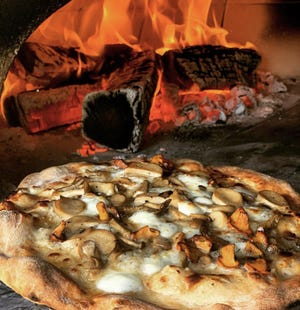 A white pizza topped with foraged mushrooms comes out of the mobile wood-fired oven of Flour Girl & Flame, a Milwaukee pizza trailer that debuted in late summer.