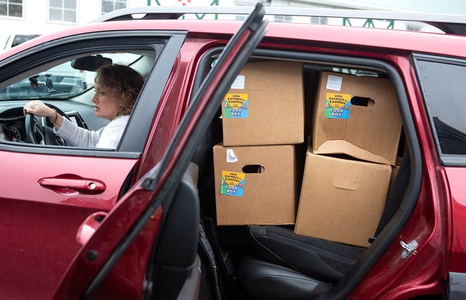 Della Stuart from the Christian Assembly Church in Newark waits, as volunteers load her car up with USDA boxes of food for 15 families Tuesday at Irongate Equestrian Center near Croton.