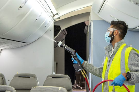 Boeing employee Arzan Dotivala uses an electrostatic sprayer to apply an approved disinfectant to a row of seats inside a Boeing mockup cabin.