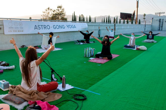 People attend a yoga class at Astro Gong Yoga Studio being held on a roof top parking lot, as the studio cannot be open to the public amid the coronavirus pandemic, August 4, 2020, in Los Angeles, California. (VALERIE MACON/AFP via Getty Images/TNS)