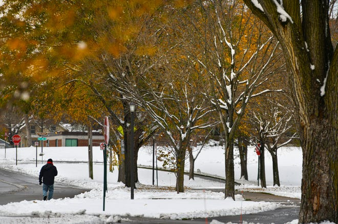 Remaining fall colors contrast with new fallen snow near the original Tech High School building Wednesday, Oct. 21, 2020, in St. Cloud. The National Weather Service reported 7 inches of snow in St. Cloud at 6 a.m. Wednesday.More snowfall is expected Thursday.