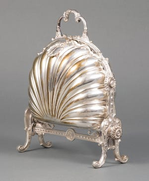 This silver-plated serving piece is called a box but it doesn't look like one. It held English biscuits, but if the sides opened, the cookies inside would fall down. Each of the shell-shaped bowls had a hinged, pierced flap that kept the heat and the biscuits in place when the sides were opened and became flat bowls to serve the cookies. The flaps are often missing when the biscuit box is sold.