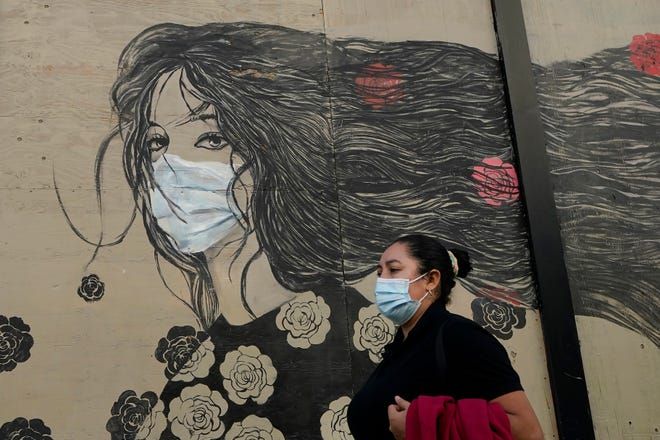 A woman wears a mask while walking past a mural of a woman in a mask during the coronavirus outbreak in San Francisco, Tuesday, Oct. 20, 2020.