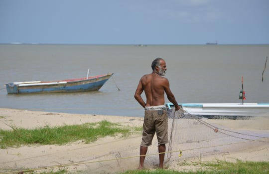 A fisherman pulls his nets from the Gulf of Paria in Trinidad and Tobago.