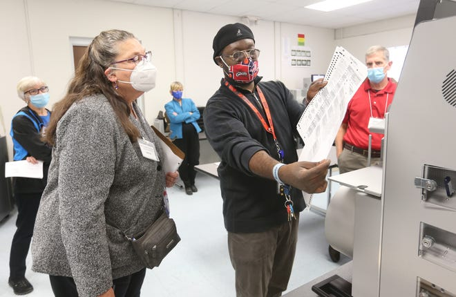 Hudson League of Women Voters member Pat Simons talks with Summit County Board of Elections network and systems administrator Kevin Moreland about a logic and accuracy test performed to check the ballot tabulation system on Thursday.