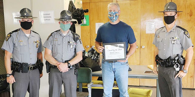 From left, Lt. Chad Enderby from the Cleveland Post of the State Highway Patrol, Sgt. Dan Kumar of the Ashland Post of the State Highway Patrol, Mark Eagle and Sgt. Brad Bishop of the Ashland Post of the State Highway Patrol during a ceremony Wednesday to added Eagle to Ohio's Saved By The Belt Club.