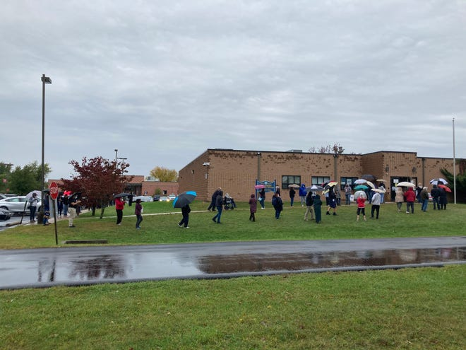 A line of voters waits in a steady rain to cast mail-in ballots for the Nov. 3 election at the Bucks County government services office in Bristol Township.