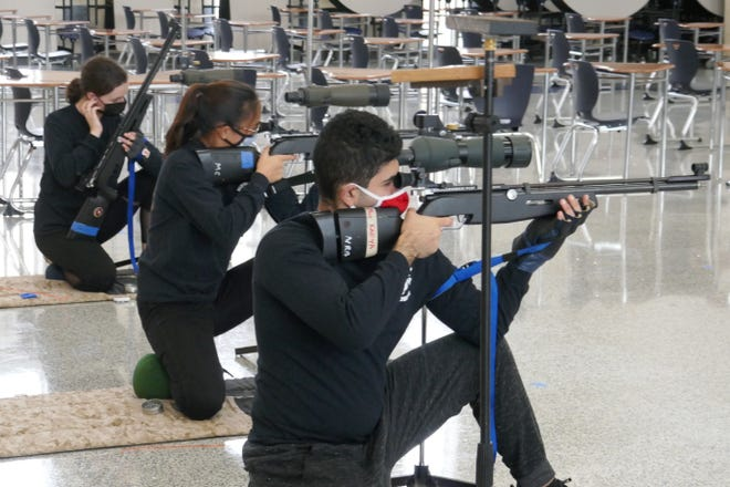 Members of the Bensalem High School Marine Corps Junior ROTC Shooting Team practice in the school cafeteria Monday.  Team members are (from left) Kaitlin Robinson,  Shayna Sit and Mohammad Kafya.