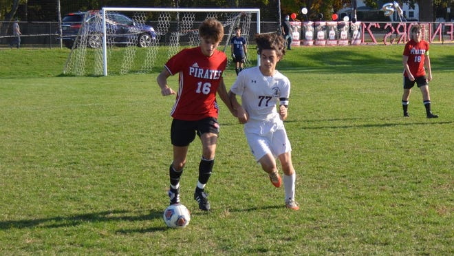 Cinnaminson's Owen Ogden (16) pushes the ball toward the touch line with Nico Yiatrou of Holy Cross in pursuit during Wednesday's Burlington County Scholastic League game.