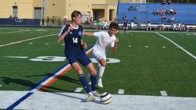 Shawnee defender Charlie Kitch (14) plays the ball upfield with Nicholas Fiore of Cherokee in pursuit.