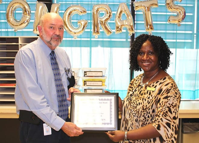 Superintendent of School Timothy Cooley presents Pam March, principal of G.W. Carver Elementary, a plaque in honor of her selection as the 2020-2021 Beauregard Parish Elementary Principal of the Year.