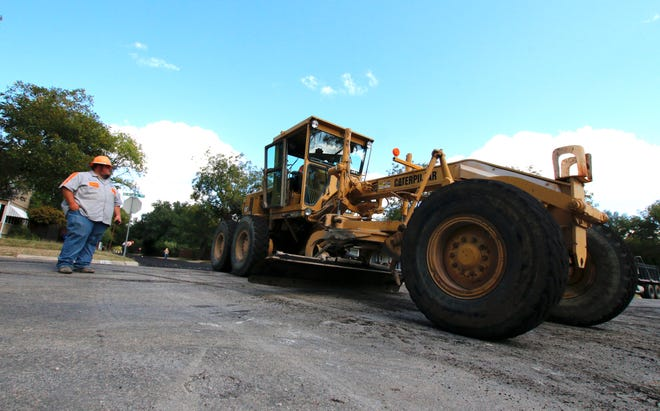 City of Brownwood Streets Department employee Michael Blanton stands in the intersection of Belmeade and Avenue M Wednesday as Alvis Eoff operates a motor grater. Street department workers have been working to repave a section of Avenue M.