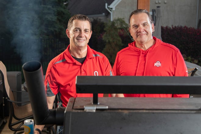 Instead of their usual parking spots in the lot just east of Ohio Stadium, Brian Hodges, left, and David Deiley fire up the meat smoker as they prepare to tailgate for Ohio State's football game against Nebraska at Hodges' house in Powell on Thursday. Hodges plans on 30-35 people in and out of his home tailgate throughout the day on Saturday.