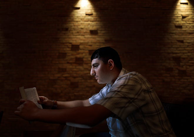 Robert Scott, 19, reads a John 3:16 quote from the Bible at Faith Memorial Church in Lancaster. Robert Scott has been involved in Central Ohio Youth for Christ's Juvenile Justice Ministry, and it changed his life.
