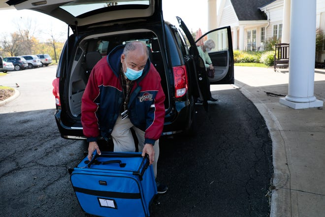 Jim Hunter, left, a poll worker with the Franklin County Board of Elections, unloads a bag containing ballots, and other voting necessities on Thursday, Oct. 22, 2020 at Mill Run Rehabilitaion Center and Assisted Living in Hilliard, Ohio. Hunter and other poll workers visit nursing homes where they help residents cast their ballot. Advocates fear that some residents of long-term care facilities could miss out on voting due to the COVID-19 outbreak and visitor restrictions.