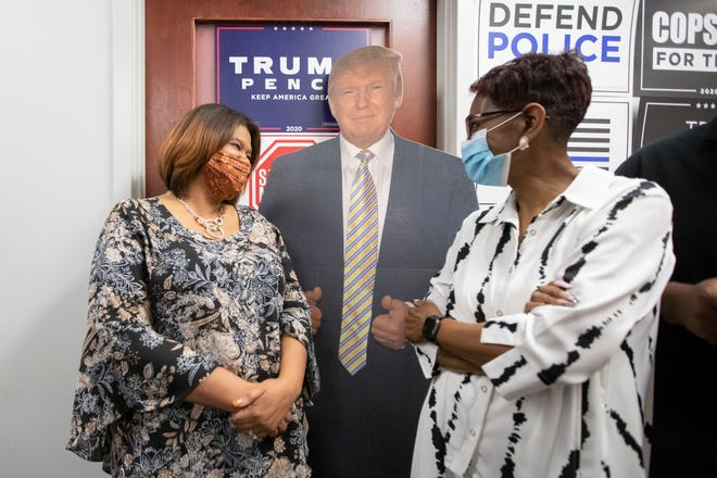 Tracy Forbes, left, and Lavonne Bailey chat beside a cardboard cutout of President Donald Trump during a Black Voices for Trump rally in Westerville on Wednesday. [Adam Cairns/Dispatch]
