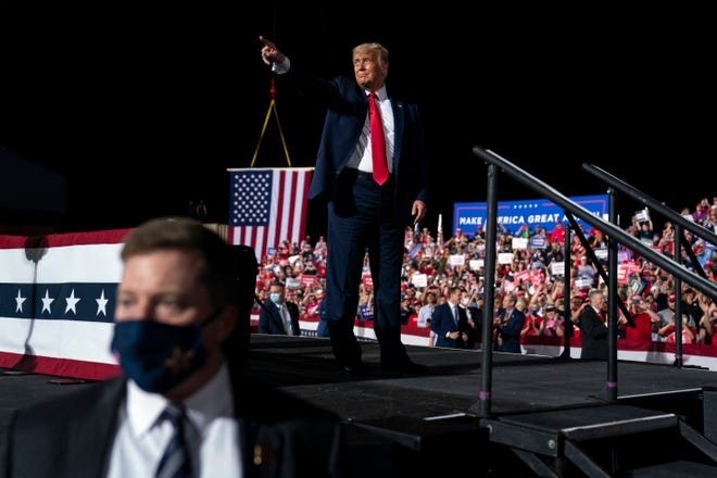 President Donald Trump points to the crowd as he walks off stage after speaking at a campaign rally Wednesday in Gastonia, N.C.