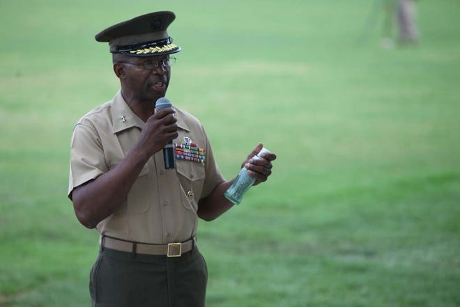 Then-Major Gen. Ronald L. Bailey, the 1st Marine Division commanding general, shows audiences a bottle of sand from Guadalcanal during a battle color rededication ceremony on the division parade field in 2012.